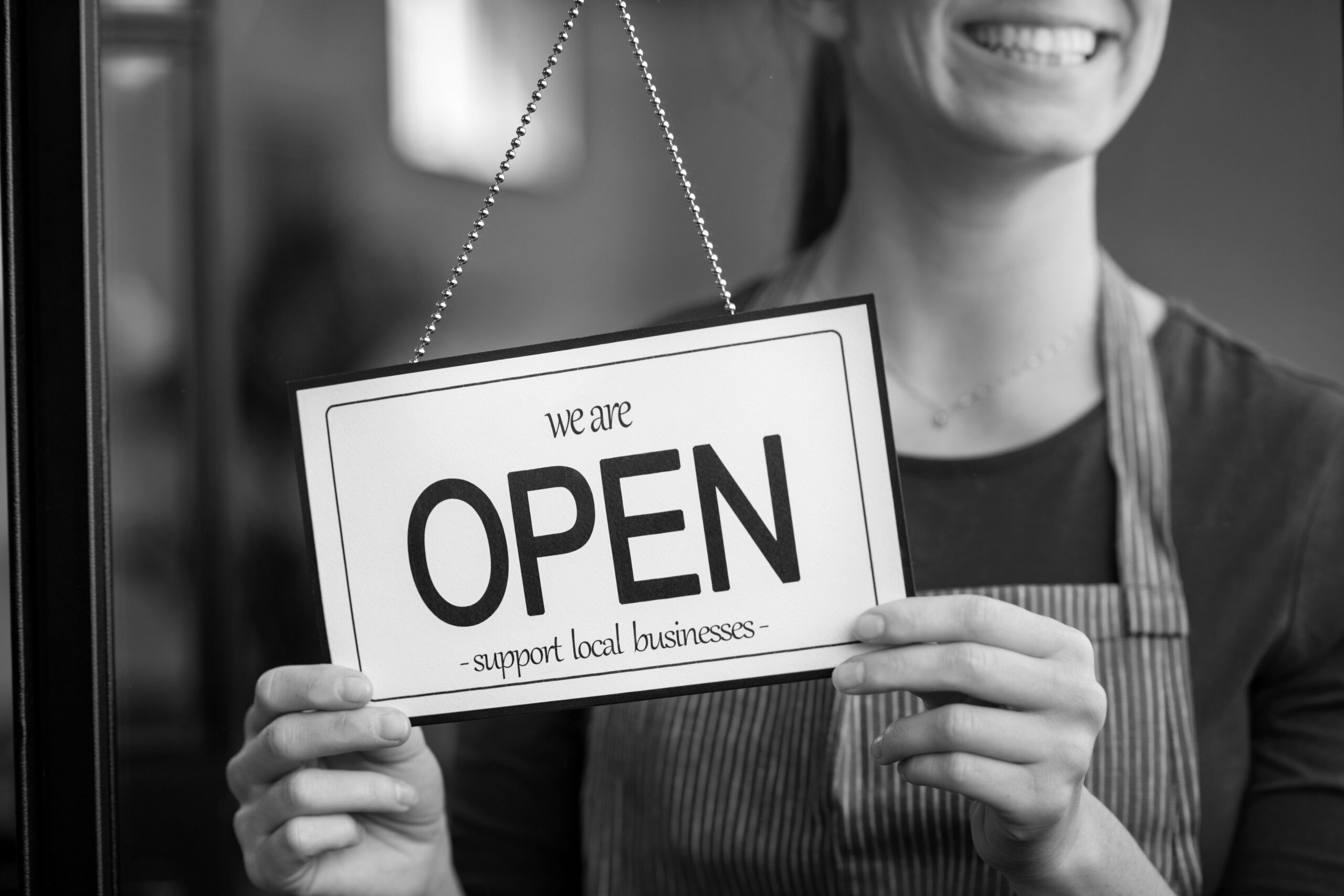 woman smiling with open sign